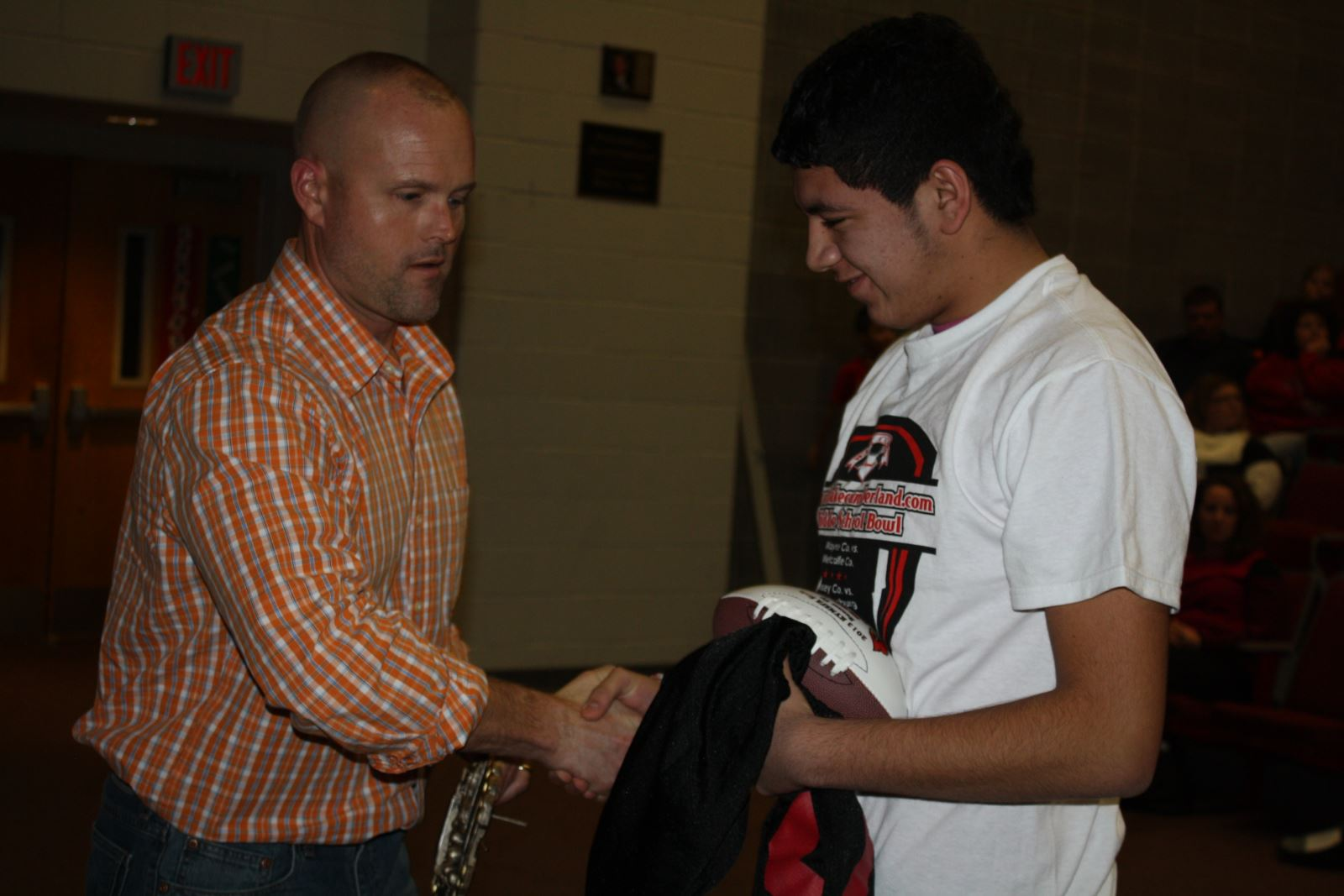 Luis calderon receving his awards from assistant coach sheridan wright