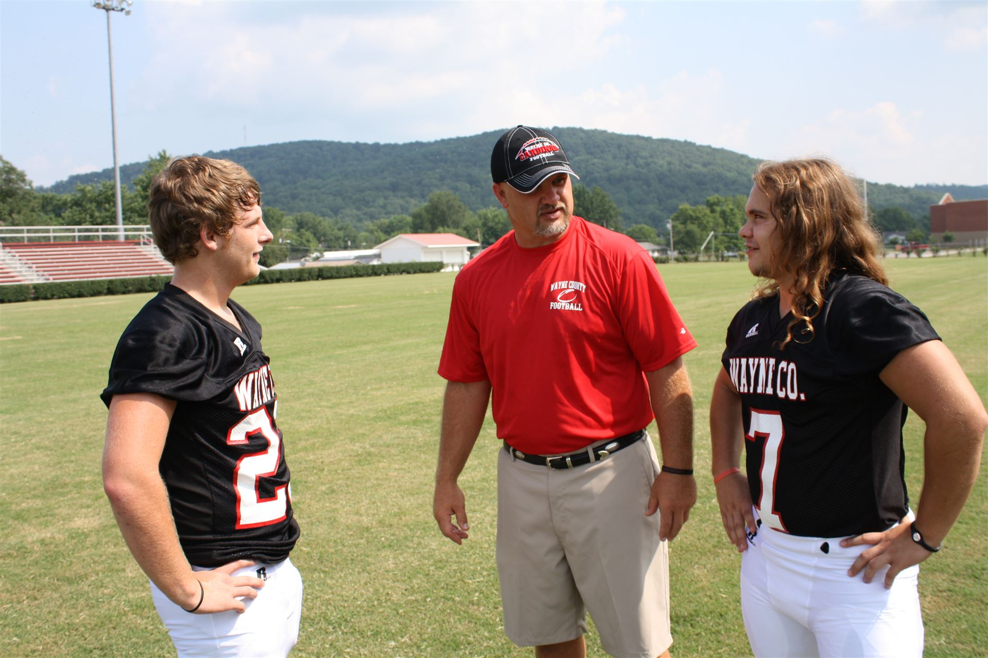 Wchs football team take photos wayne county high school shawn thompson talks to player john gregory and chris wright thecheapjerseys Images