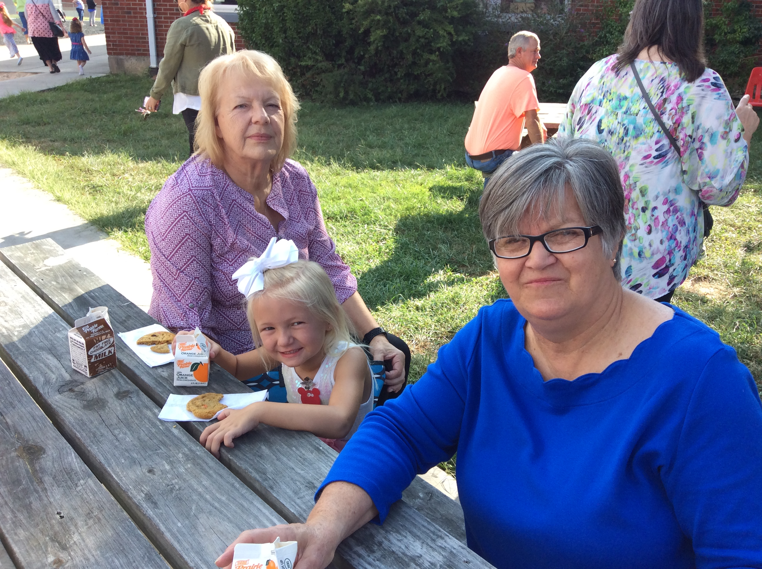 Sue Thompson and Phyllis Flowers sit with granddaughter Pyper Thompson while she finishes her cookie.