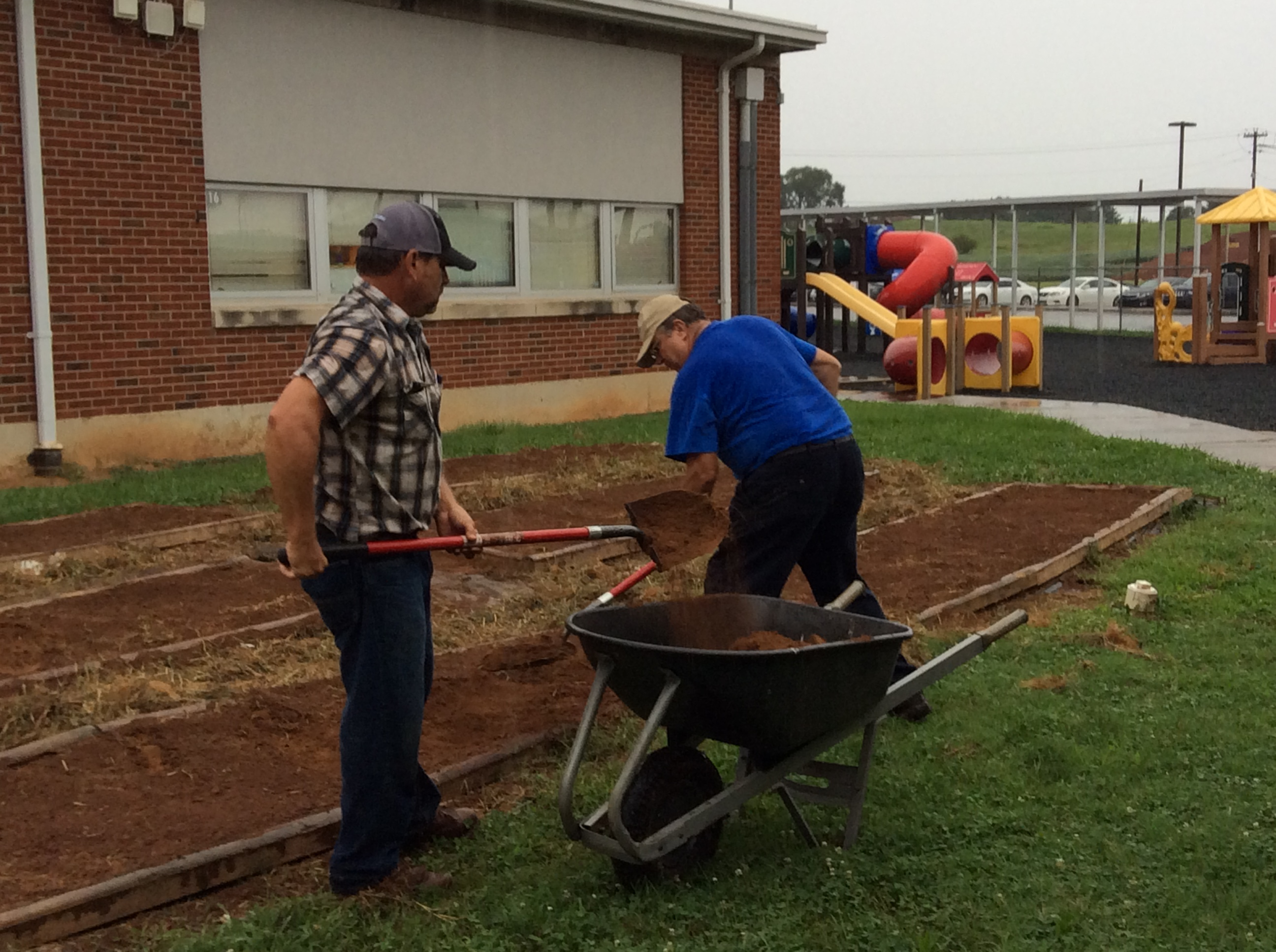Glen Roberts and Terry Bertram putting soil in the beds.