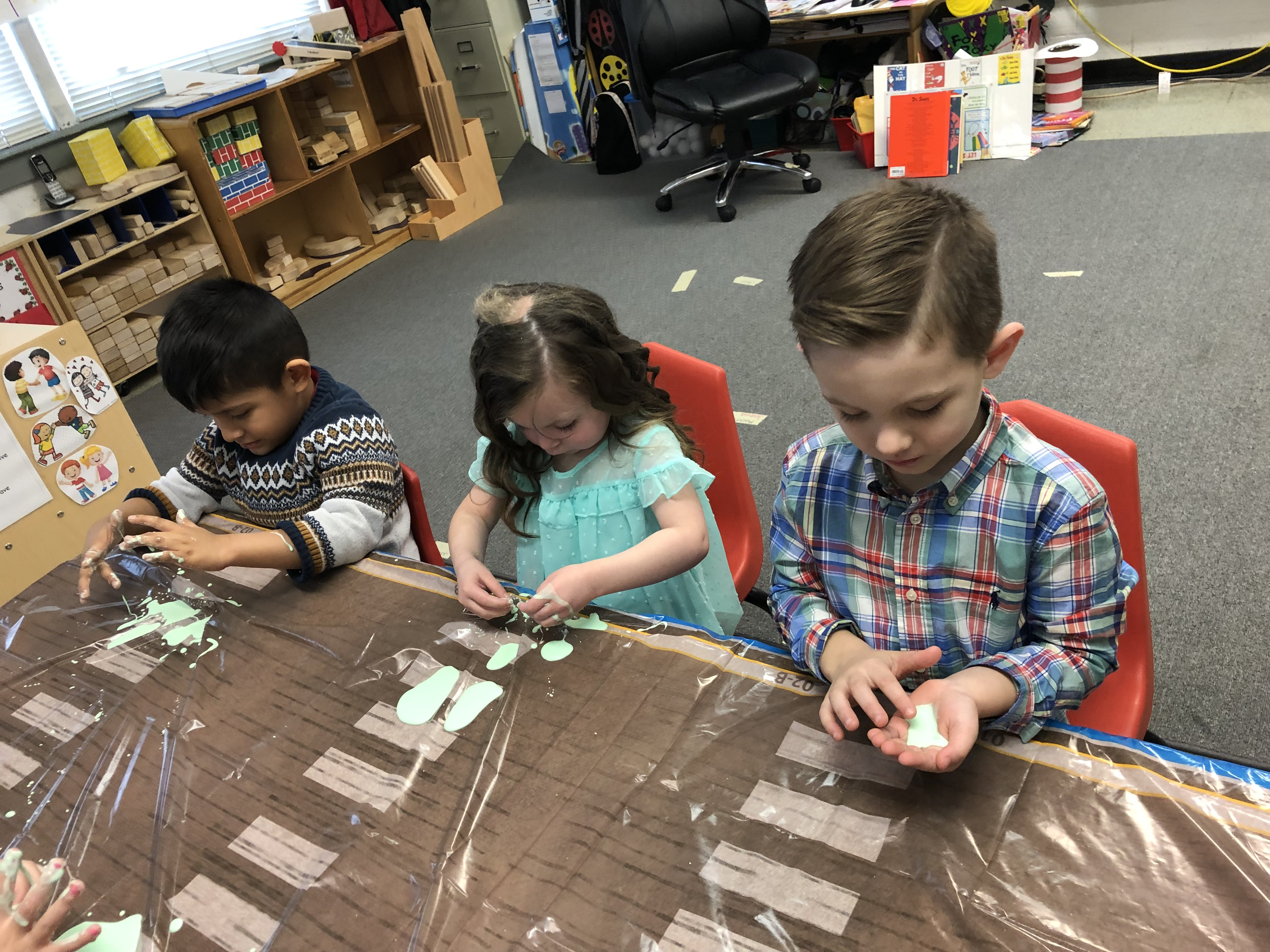 "(L-R) Joshua Santiz Martinez, Bella Foster, and Easton Dishman experimenting with Oobleck after listening to the story, ""Bartholomew and the Oobleck"" read by preschool red group teacher Nikki Prince"